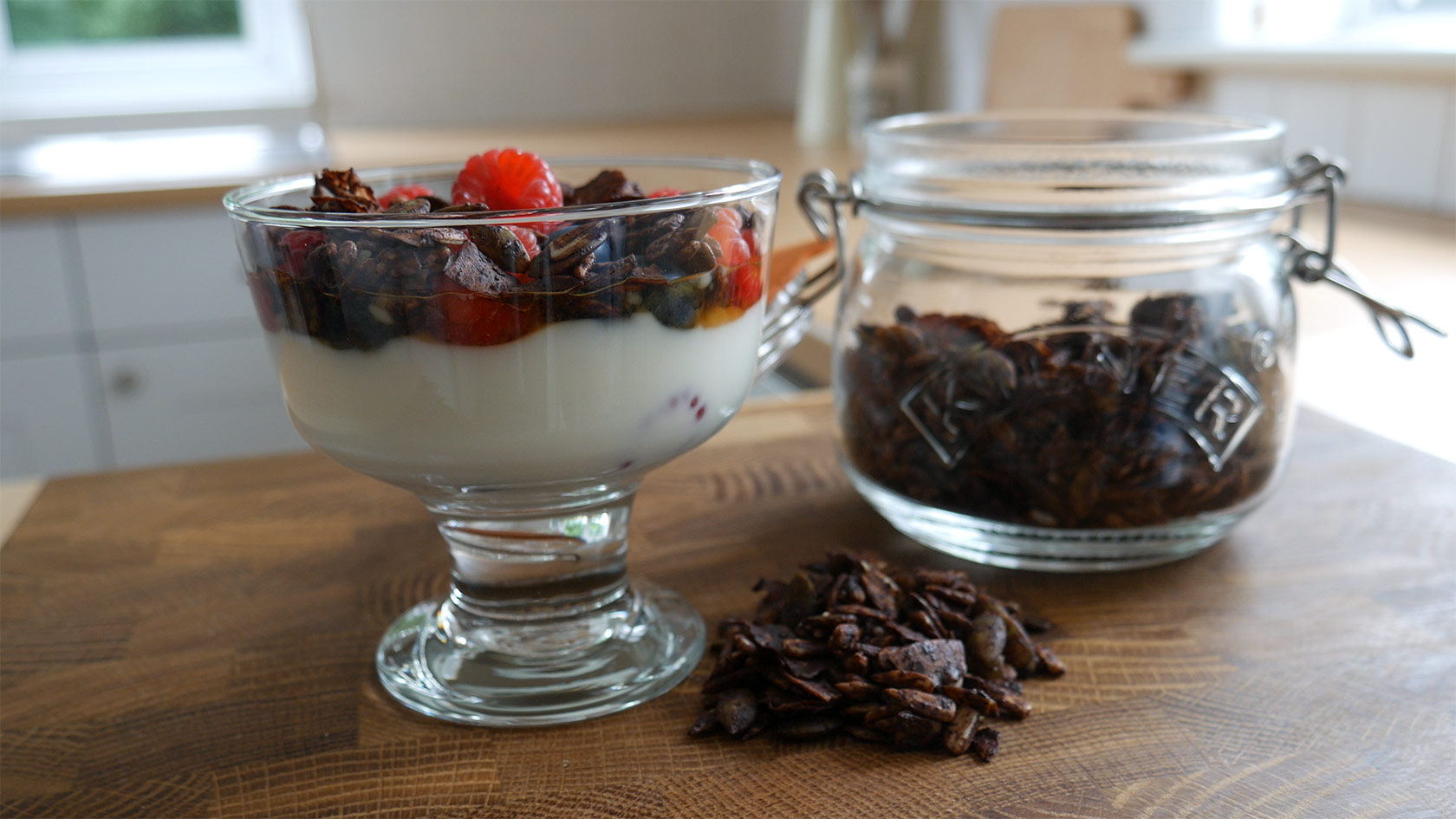 A bowl of yogurt topped with berries and chocolate crunch topping.